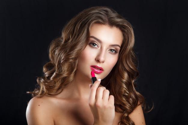 Charmante jonge vrouw die rode lippenstift toepast. foto van mooie vrouw met perfecte huid