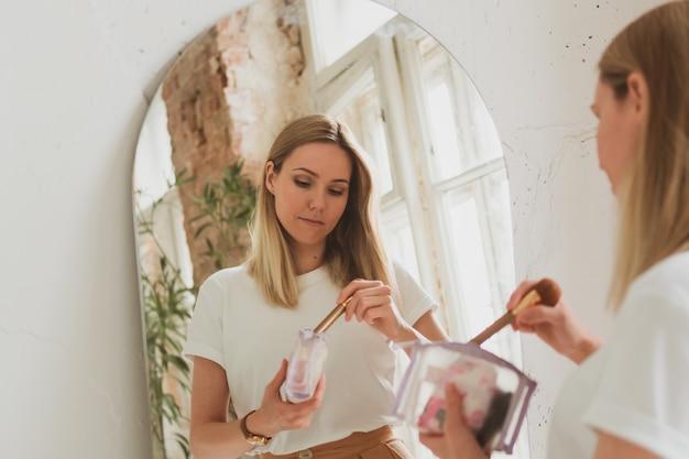 Charmante jonge vrouw die thuis make-up aanbrengt in de buurt van de spiegel