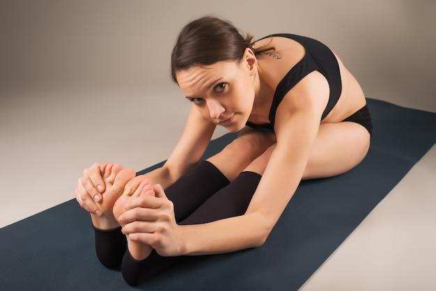 Charmante jonge vrouw doet zich het uitrekken vóór oefening zittend op een tapijt op de vloer