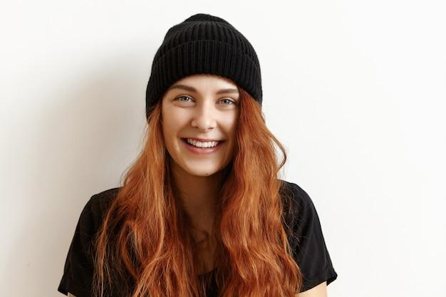 Charmante jonge vrouw, gekleed in stijlvolle zwarte hoed en t-shirt met vrolijke blik