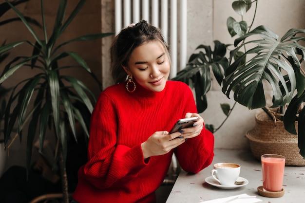 Charmante jonge vrouw in enorme oorbellen en lichte trui chats in telefoon zittend in café tijdens een kopje koffie
