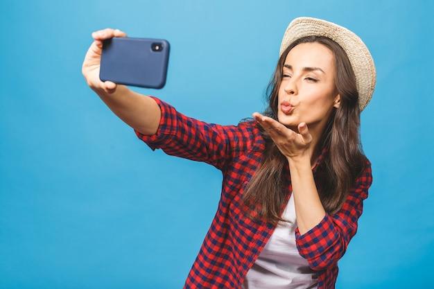 Charmante jonge vrouw in witte hoed reizen en selfie te nemen