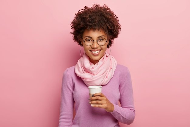 Charmante jonge vrouw met afro kapsel, drinkt afhaalkoffie uit wegwerpbeker