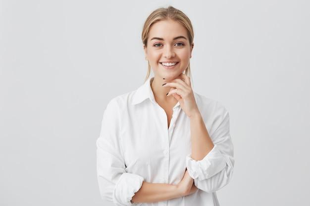 Charmante jonge vrouw met blond steil haar, gekleed in een wit overhemd dat aangenaam in de camera kijkt en haar kin aanraakt. jong mooi meisje met het brede glimlach stellen.