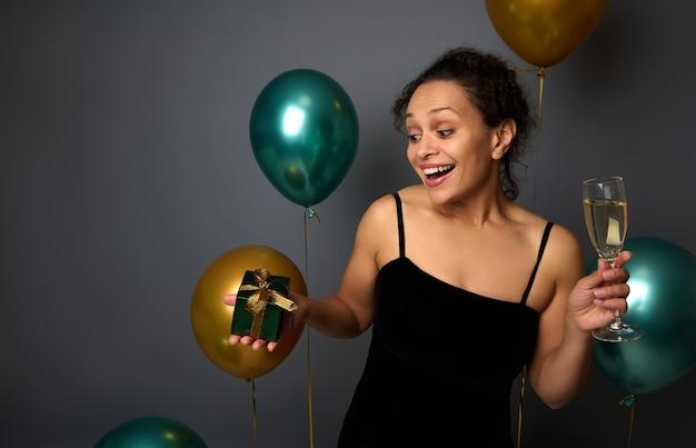 Charmante jonge vrouw met een glas champagne in haar handen die zich schattig verheugt over het kerstcadeau, poserend op een grijze achtergrond versierd met ballonnen van goud en groene kleur met kopieerruimte voor advertentie