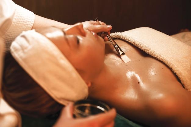 Charmante jonge vrouw met een huidverzorging procedures op gezicht en lichaam in een spa salon.