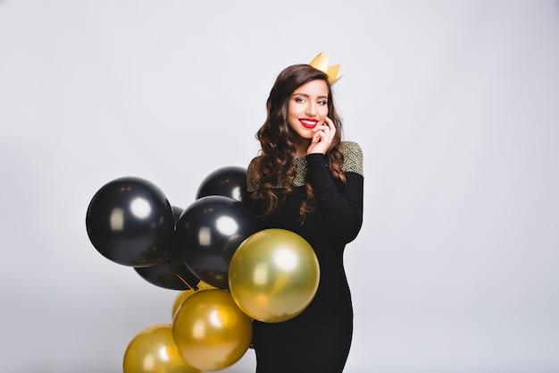 Charmante jonge vrouw met gouden en zwarte ballons, die zwarte manierkleding en gele kroon dragen. feestdagen, nieuwjaarsfeest, gelukkige verjaardag, plezier maken, glimlachen.