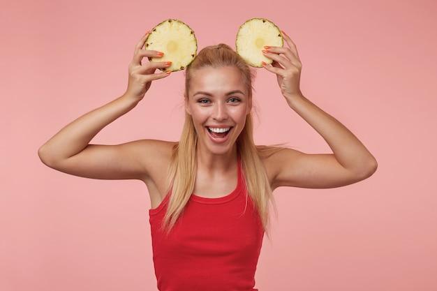 Charmante jonge vrouw met lang blond haar poseren in rood shirt, plezier maken met ringen van verse ananas, vreugdevol glimlachen