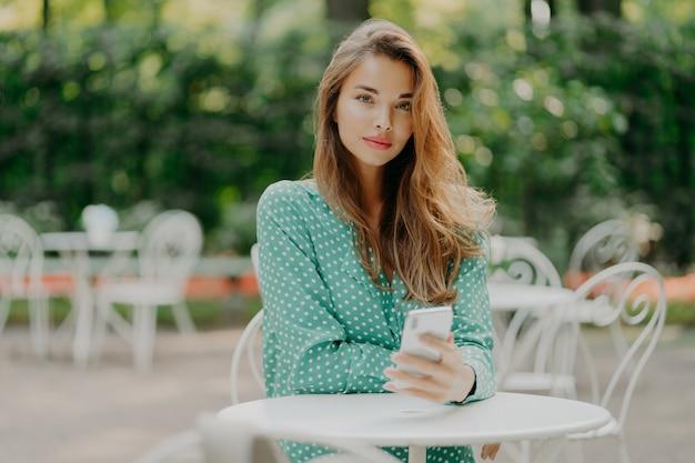 Charmante jonge vrouw met lang haar, draagt polka dot groen shirt en zit aan tafel in terras