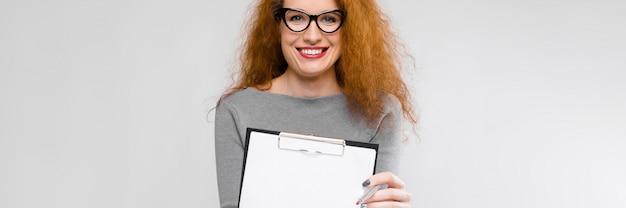 Charmante jonge vrouw met rood haar. een jonge vrouw in een grijze trui. een jonge vrouw met een bril heeft een pen en een notitieboekje in haar handen