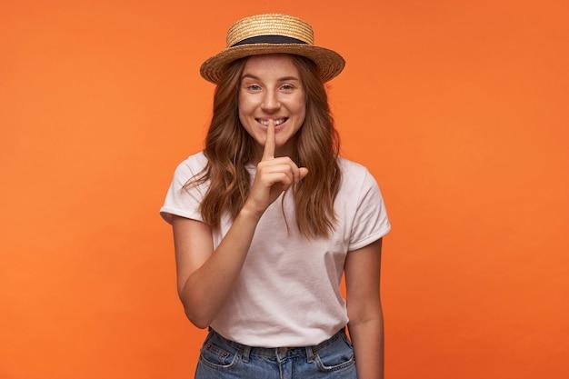 Charmante jonge vrouw op zoek met oprechte glimlach en wijsvinger opheffen naar haar lippen, geïsoleerd