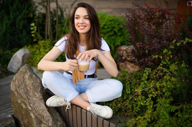 Charmante jonge zakenvrouw met koffiepauze zittend op café terras.