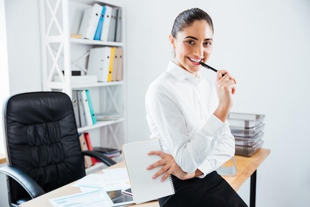 Charmante jonge zakenvrouw zittend op de tafel op kantoor en kijkend naar de voorkant