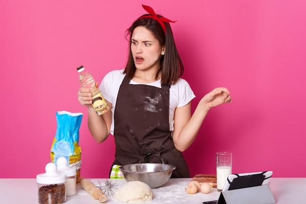 Charmante jongedame die bakkerij maakt in de keuken, veel ingrediënten en gebruiksvoorwerpen gebruikt om deeg te kneden, kijkt met verbazing op een fles olie, gebruikt een tablet om nieuwe recepten te maken. kopieer ruimte.