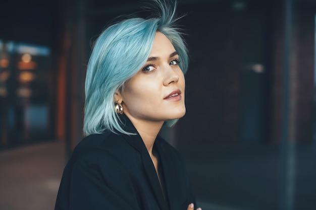 Charmante jongedame met blauw haar poseren buiten en kijken naar voorzijde met een gebouw op de achtergrond