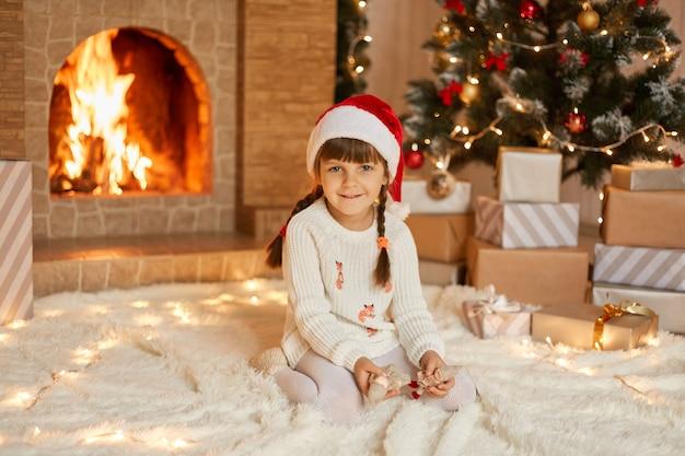 Charmante jongen in kerstmuts en witte trui zittend op een tapijt in de buurt van kerstboom en open haard