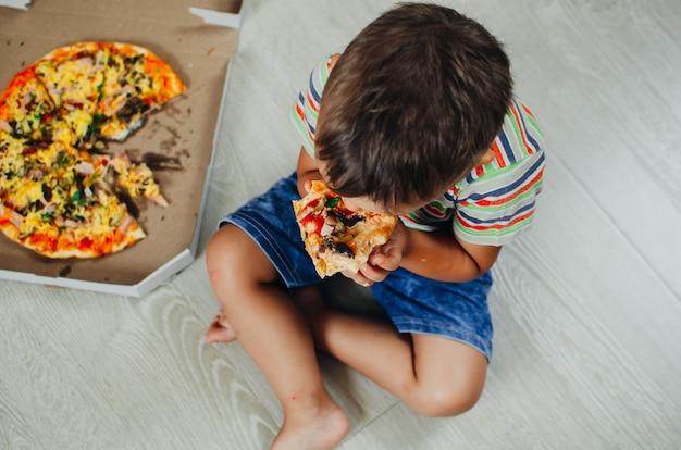 Charmante jongen zittend op de vloer pizza bovenaanzicht eten