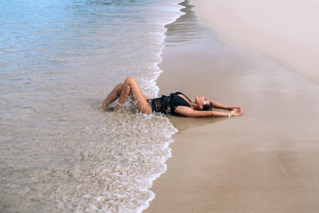 Charmante juffrouw in een stijlvol zwart zwempak en lichte make-up ligt en ontspant het strand. vrije tijd en reizen