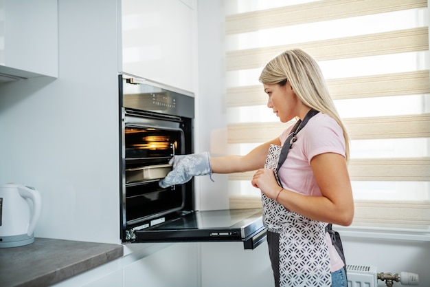 Charmante kaukasische blonde vrouw in schort die uit oven gebakken voedsel nemen. binnenlandse keuken interieur.