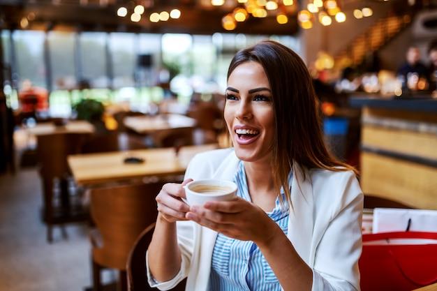 Charmante kaukasische lachen brunette zitten in de cafetaria