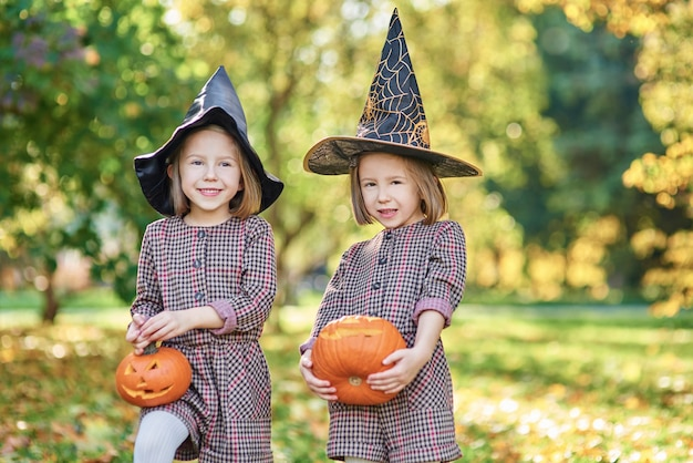 Charmante kinderen in heksenkostuum met halloween-pompoenen