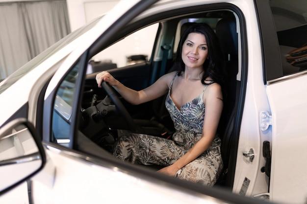 Charmante klant donkerbruin zittend in haar nieuwe auto net gekocht in dealeship center