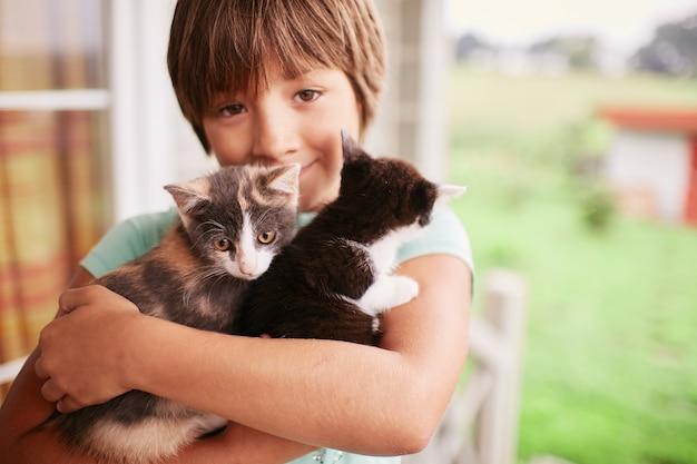 Charmante kleine jongen houdt twee poesjes in zijn armen