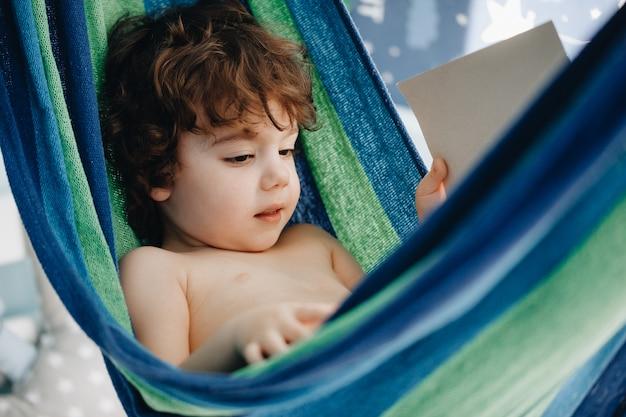 Charmante kleine jongen met krullend haar rust in een hangmat in de kinderkamer