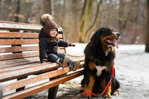 Charmante kleine jongen zit op de bank met een berner sennenhond