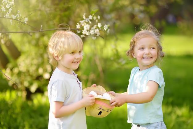 Charmante kleine kinderen jaagt voor beschilderde eieren in het voorjaar park op paasdag.