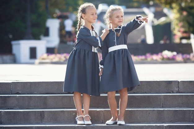 Charmante kleine meisjes in retro jurk wandelen in de stad op een zonnige zomerdag. een echte smaak van schoonheid voor meisjes. gelukkige jonge geitjes in uniforme glimlach buitenshuis.