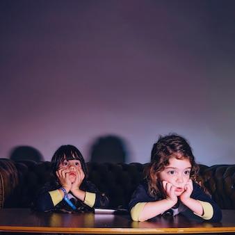 Charmante kleine meisjes kijken naar film