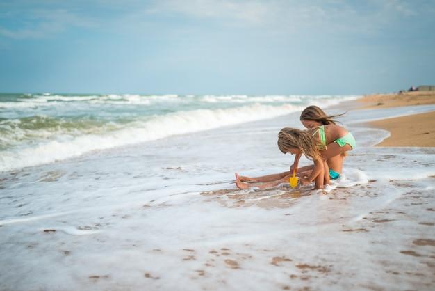 Charmante kleine meisjes zusjes zwemmen en spetteren in de golven van de zee op een zonnige warme zomerdag tijdens vakantie