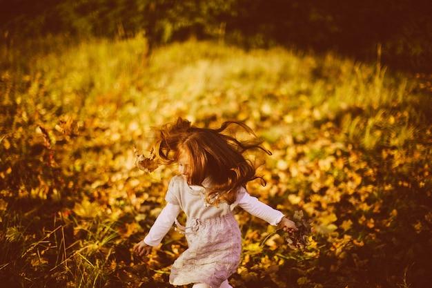 Charmante kleine meisjeslooppas in lang de herfstgras