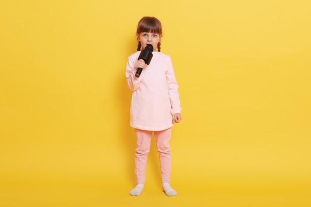 Charmante kleine sterzanger met microfoon in handen sin gin g liedjes geïsoleerd op gele achtergrond, kijkt naar de camera, volledige lengte foto van kleine schattige zanger concert regelen.