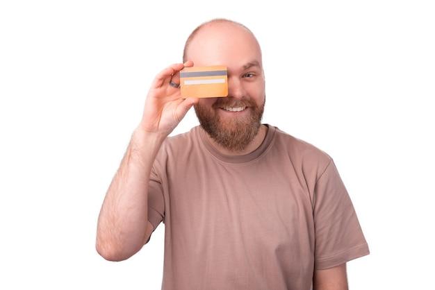 Charmante knappe jonge bebaarde man met creditcard op de ogen en glimlachen