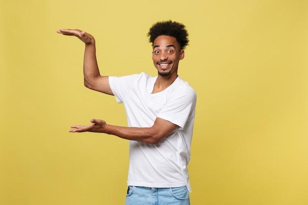 Charmante knappe jonge zwarte man die zijn hand omhoog houdt om het huidige verkoopproduct te tonen