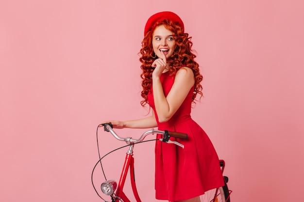 Charmante kokette vrouw in goed humeur kijkt sluw zijdelings, poseren met fiets op roze ruimte.
