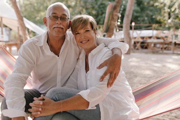 Charmante kortharige dame in blouse en spijkerbroek glimlachen, camera kijken en knuffelen met oude man in brillen en wit overhemd op strand.