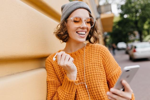 Charmante kortharige dame in grijze hoed die zich naast muur met smartphone bevindt