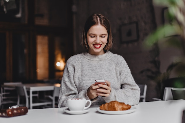 Charmante kortharige meisje in grijze trui glimlacht en chats in de telefoon. portret van vrouw in café aan tafel met croissant, koffie en retro camera.