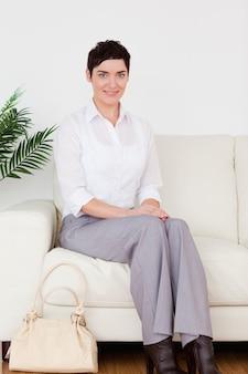 Charmante kortharige vrouw, zittend op een bank