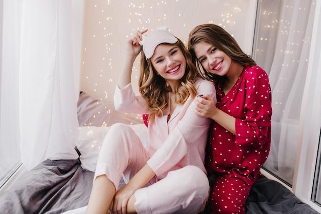 Charmante krullende meisjeszitting met gevouwen benen op haar bed en glimlachen. portret van mooie donkerharige dames omarmen in goedeweekendochtend.