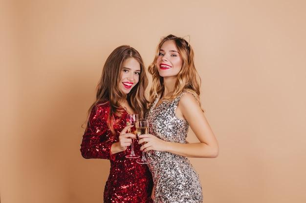 Charmante krullende vrouw in rode outfit poseren op nieuwjaarsfotoshoot met beste vriend en lachen