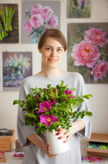 Charmante lachende jonge blanke vrouw kunstenaar houdt een vaas in haar handen met een prachtige bloeiende rozenbottel op de achtergrond van haar werkplek met bloemenschilderijen. kunst concept