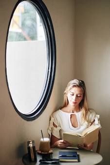 Charmante lachende jonge vrouw aan tafel zitten en interessante roman lezen