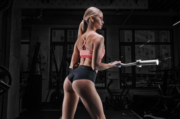 Charmante lange atleet poseren in de sportschool met een barbell in haar handen. achteraanzicht. het concept van sport, bodybuilding, fitness, aerobics, stretching.