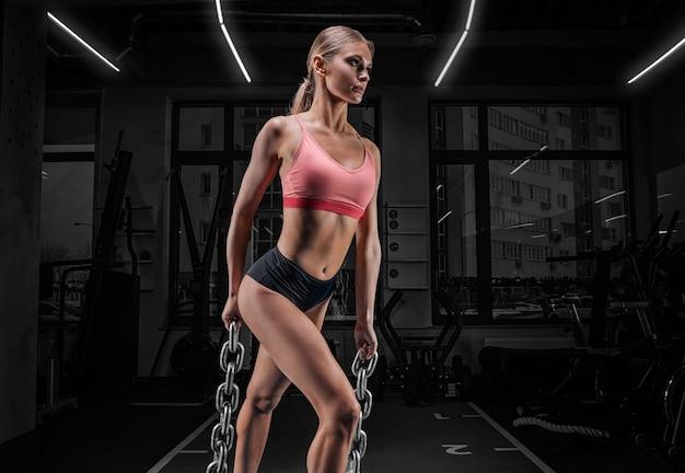 Charmante lange sportvrouw poseren in de sportschool met kettingen. het concept van sport, bodybuilding, fitness, aerobics, stretching.