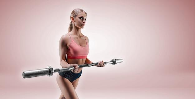 Charmante lange sportvrouw poseren in de studio op een roze achtergrond met een barbell in haar handen. het concept van sport, bodybuilding, fitness, aerobics, stretching.