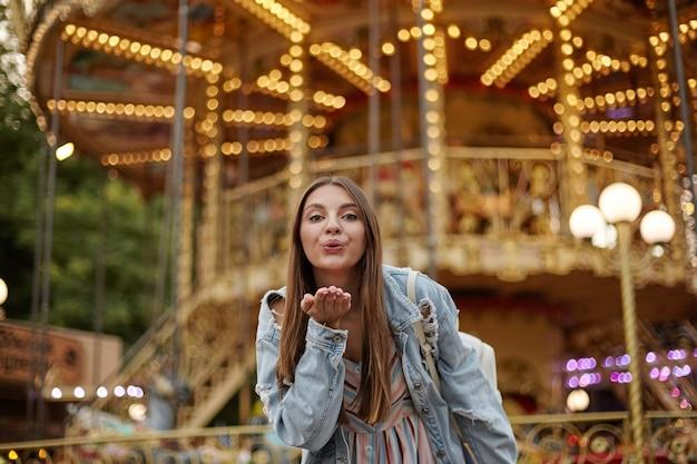 Charmante langharige jonge dame in trendy jeans vacht palm verhogen en blazen lucht kus, permanent over carrousel in park van attracties